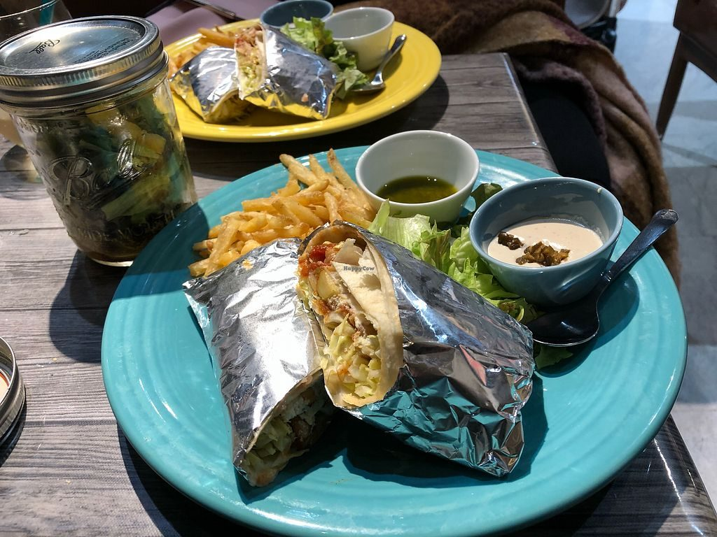 Hideout Burrito's vegan burrito served with vegan sauce and fries.