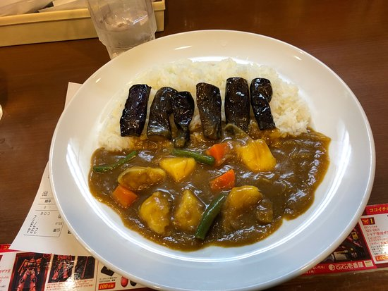 Vegetable curry with rice and cooked eggplant.