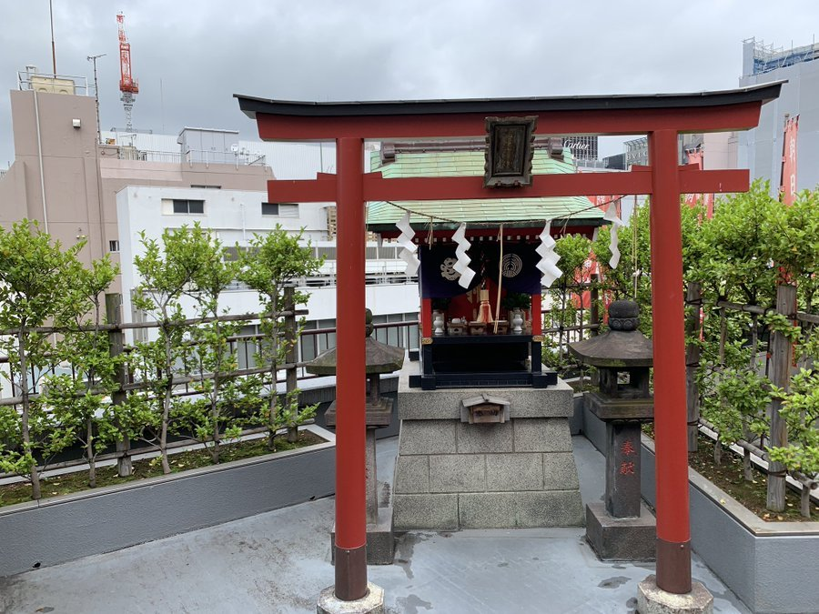 The rooftop shrine located in ginza in real life with small red gate and prayer box.